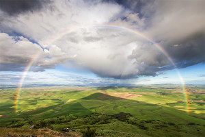 A full rainbow frames the extended shadow of Steptoe Butte, Palouse, Washington